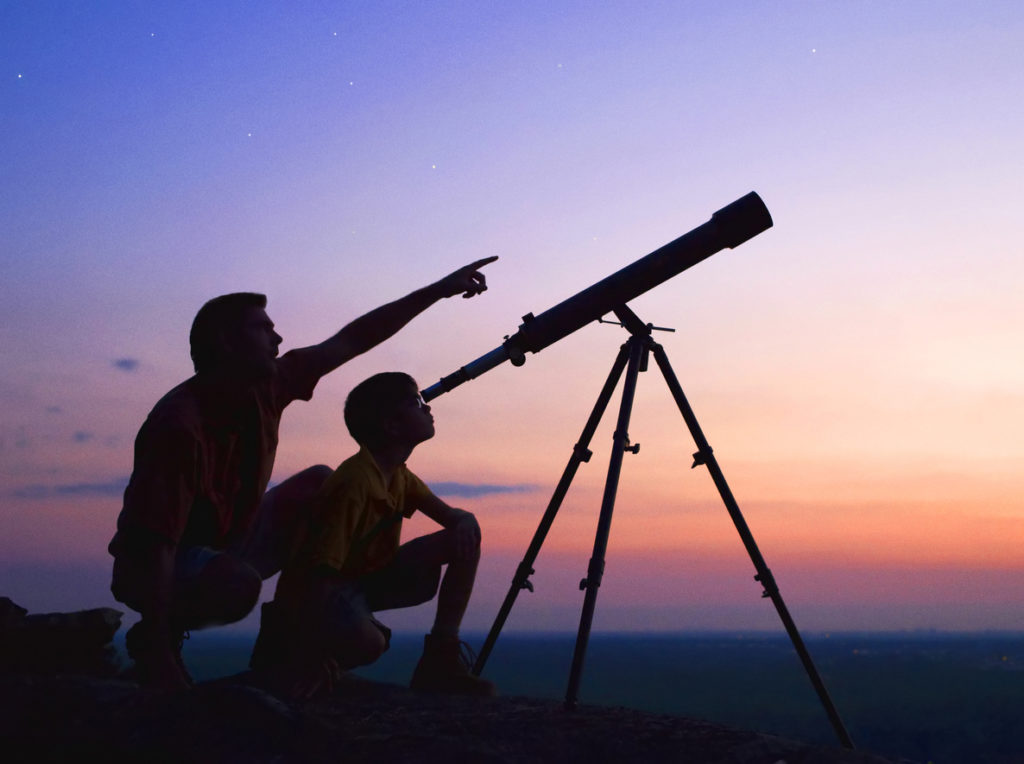 A young boy looking thru a telescope at sunset with his father.