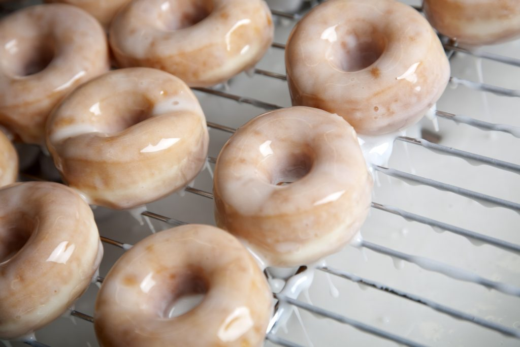 Preparing donuts in a bakery putting on the glaze