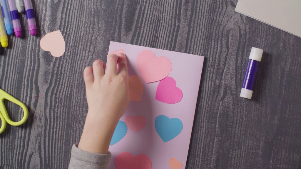 Girl's hands glueing a card. Valentine's Day