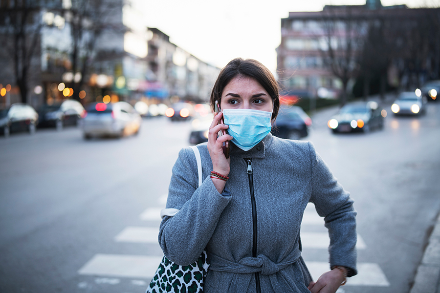 A woman waering a mask walking in the street
