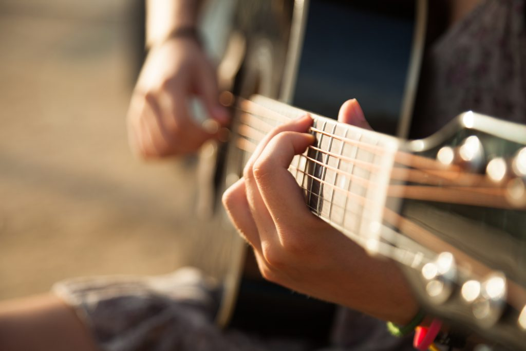 Teen girl playing acoustic guitar, detail, shallow DOF.