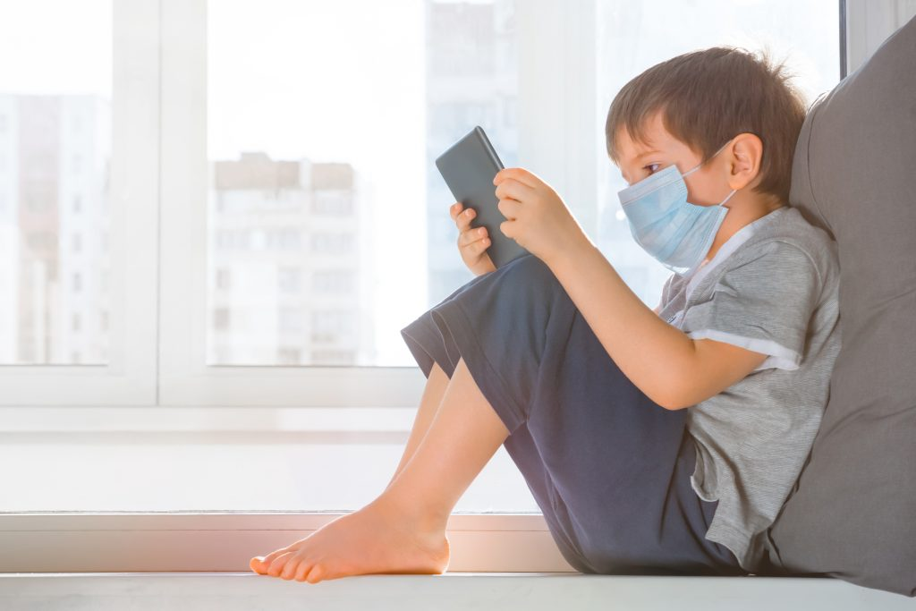 Child in protective medical mask sits on windowsill and looking at screen tablet. Kid in medical mask studying online. Studying during quarantine. E learning concept. Spending time during COVID-19.
