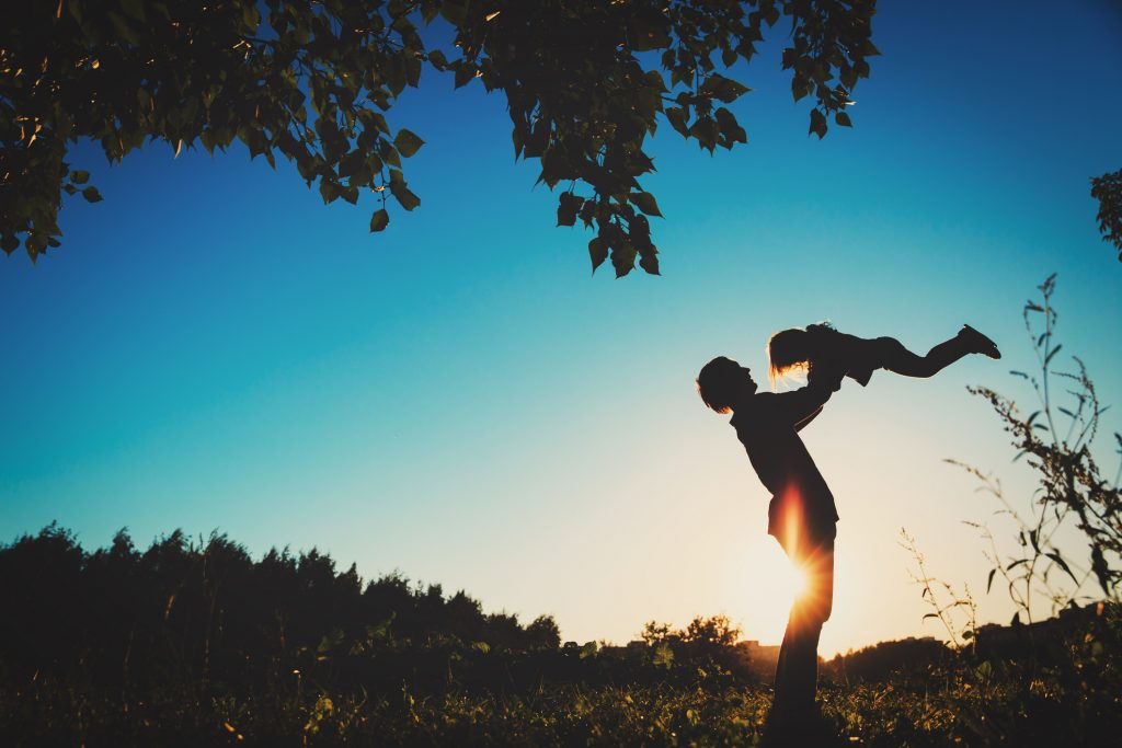 Father and little daughter silhouettes play in sunset nature