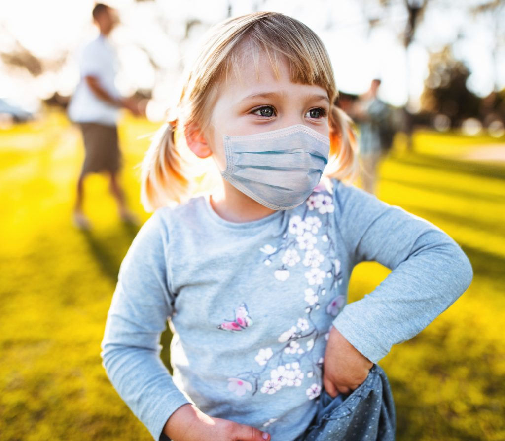 little girl playing at the park with the protective mask