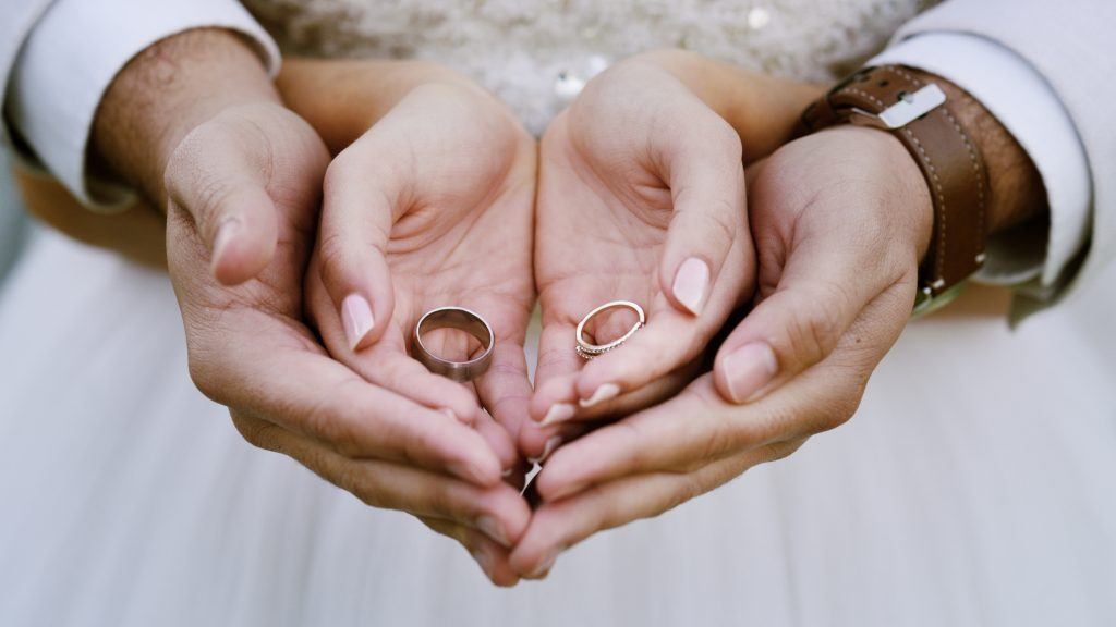 Cropped shot of a couple holding their wedding rings after getting married