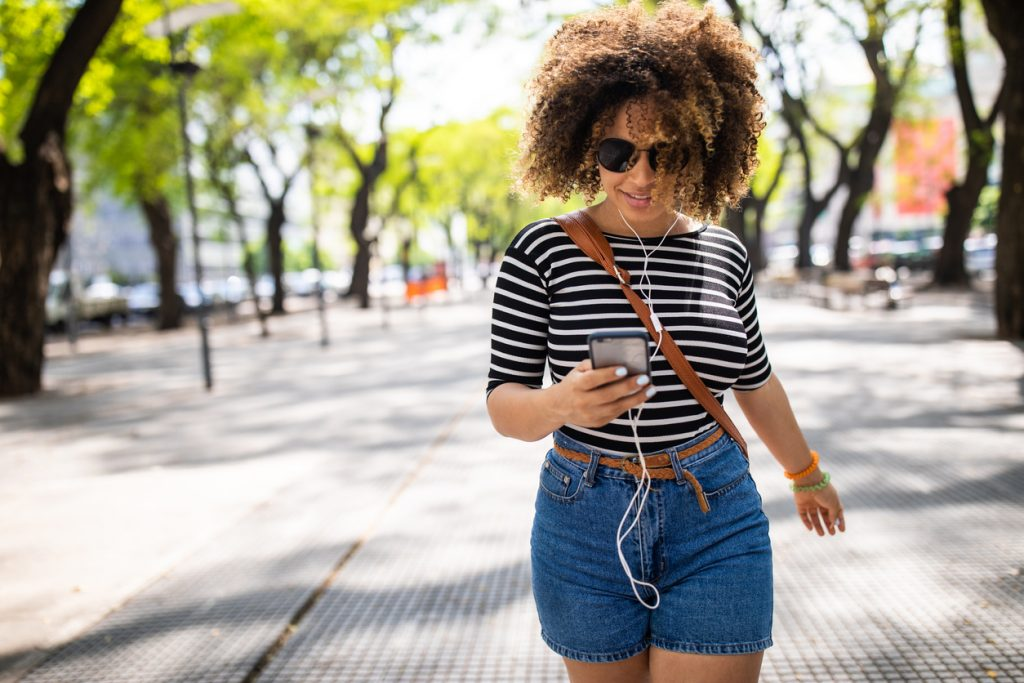 Young beautiful hipster woman walking down the street and listening music on phone