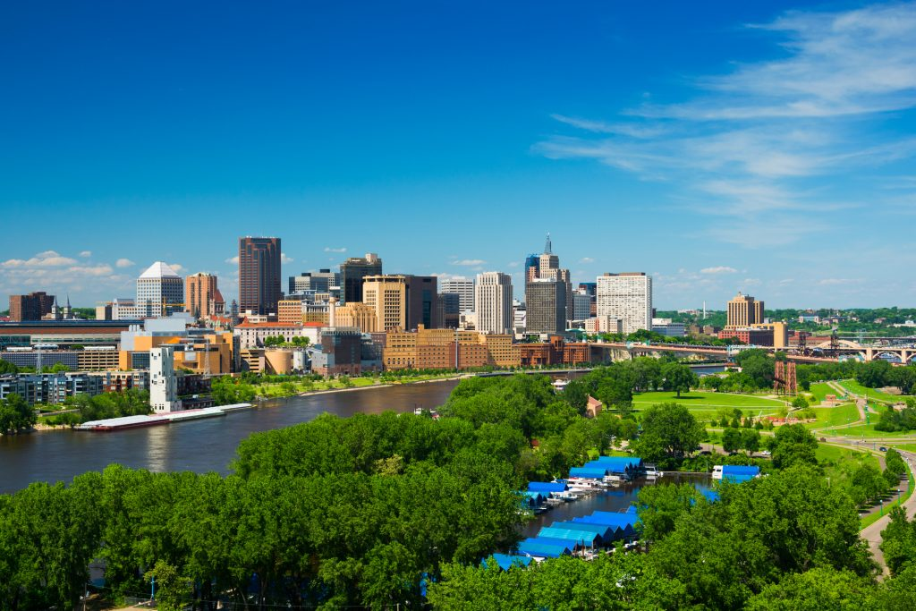 Saint Paul, Minnesota skyline with the Mississippi River, a riverfront park full of trees, a small harbor, a bridge, and a blue sky with clouds. Saint Paul is part of the Minneapolis / Saint Paul Twin Cities Metropolitan area.