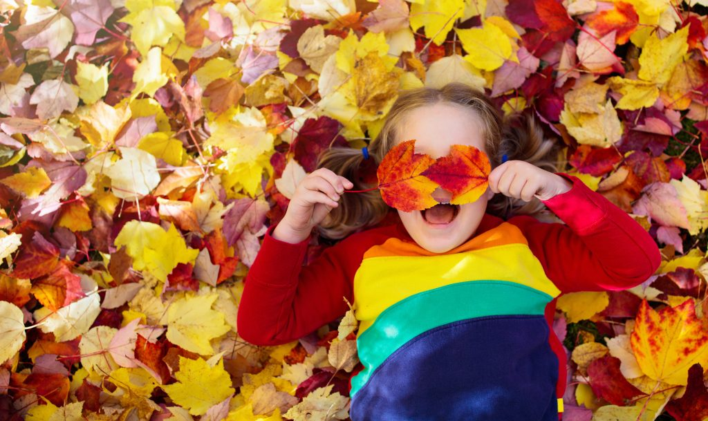 Kids play in autumn park. Children throwing yellow and red leaves. Little girl with oak and maple leaf. Fall foliage. Family outdoor fun in autumn. Toddler kid or preschooler child in fall.