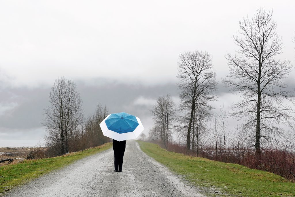 lonely woman with umbrella walking on country road