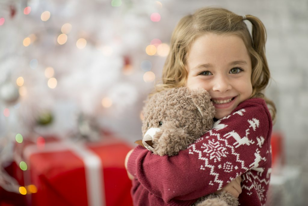 A young Caucasian girl is indoors in a living room on Christmas day. She is wearing festive clothing. She is sitting in front of a Christmas tree and hugging her new teddy bear.