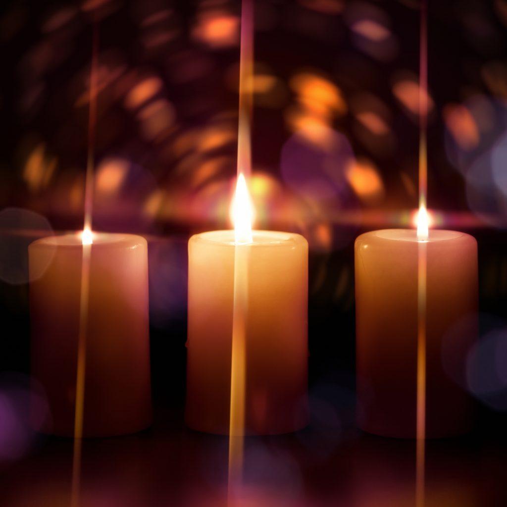 Burning candles over defocused lights