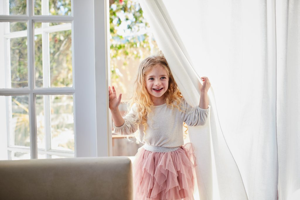 Smiling little girl wearing a tutu looking in through patio curtains from her backyard patio at home