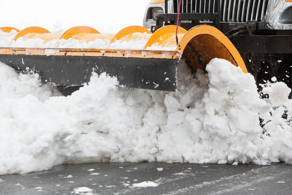 A large public works plow is clearing snow from a city street.