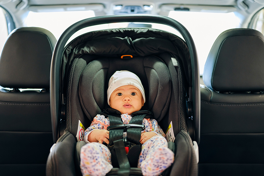 A 3 month old baby sitting in a carseat in the backseat of an auto.