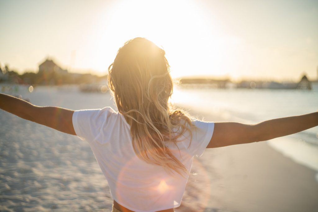 Cheerful young woman embracing nature at sunset; female standing on beach arms outstretched, Cancun, Mexico