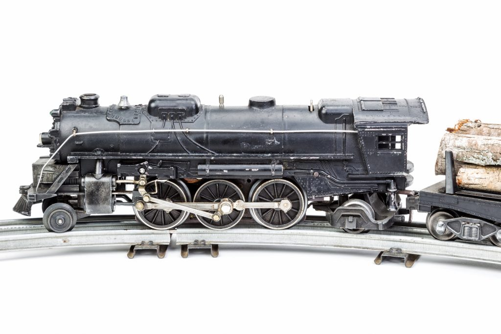 Vintage model train engine with a log car.