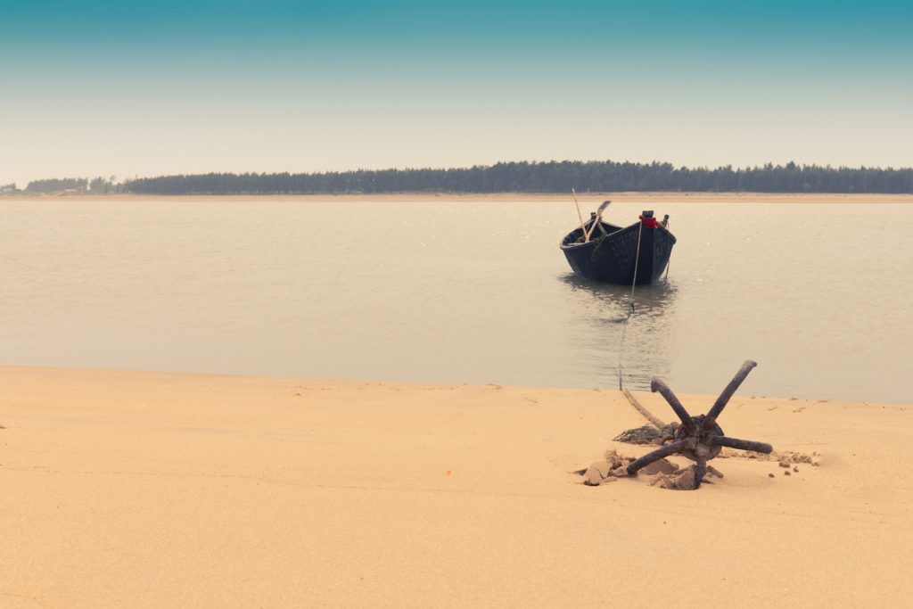 Moody image of a boat on water tied by a rope with an anchor on river bed at Tajpur, West Bengal, India. Minimalistic image.