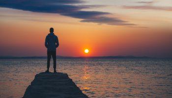 Young man enjoys the sunset at the dock