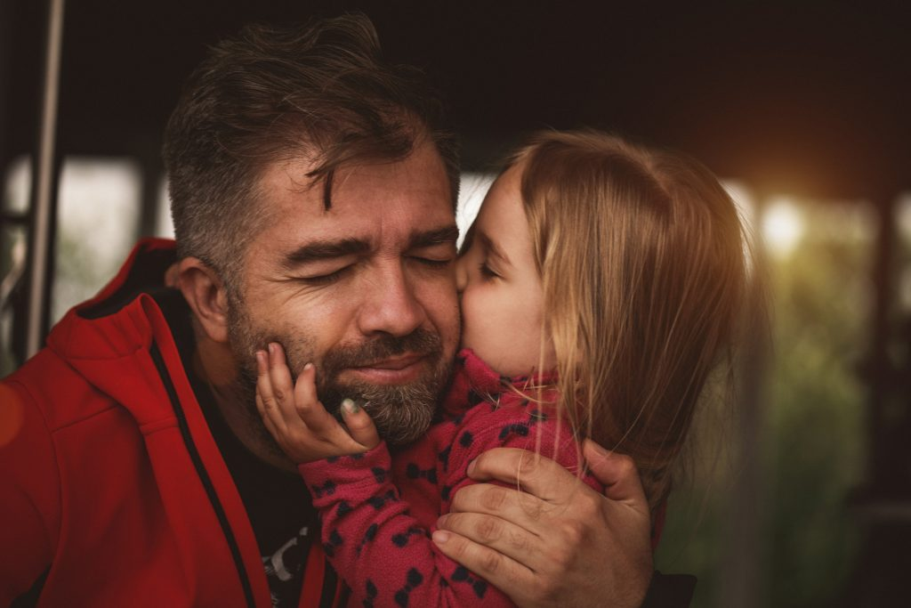 Shot of happy mid adult man embracing his adorable little daughter and enjoying with his eyes closed in a moment of bonding in affection while she is kissing him on a cheek.
