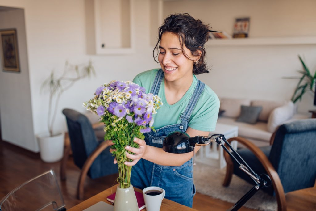 Young woman putting a fresh flower bouquet into the vase.