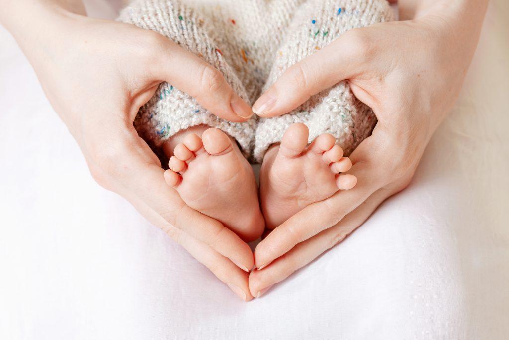 Tiny Newborn Baby's feet on female Heart Shaped hands closeup.