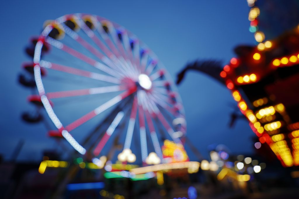 A Ferris wheel on a fairground at night with the lights shining very brightly all around.