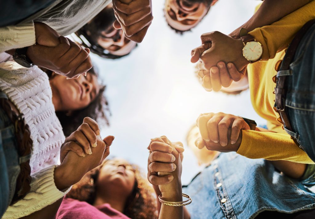 A group of Christians holding hands and praying while standing in a circle.