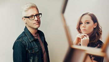 Matt Maher standing against a beige wall with Sarah Reeves in a mirror