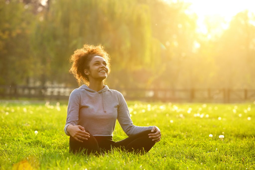 Happy young woman sitting cross legged in the grass and the sun is shining golden light through the trees.