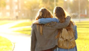 Two girls walking with their arms around each other's shoulders
