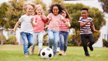 A group of children chasing a soccer ball