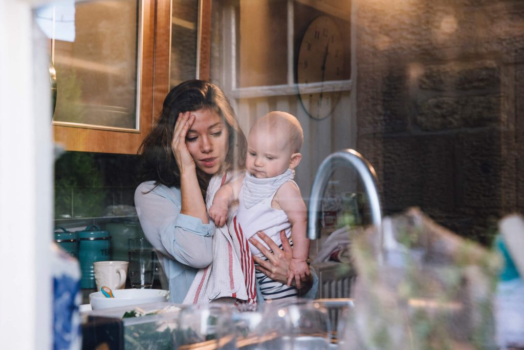 A stressed mother in a messy kitchen as she holds her baby