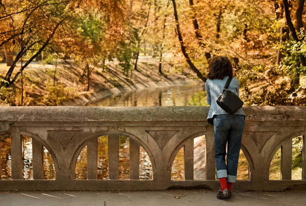 A woman thoughtfully looking out over a river while she stands on a bridge during Autumn